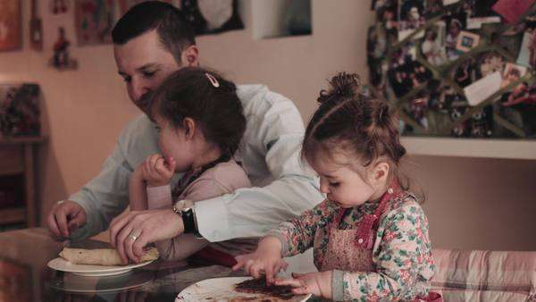 Girls enjoying pancake with father at table Royalty-free stock video
