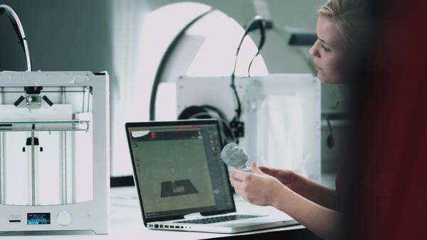 Female designer looking at 3D printed object in studio Royalty-free stock video