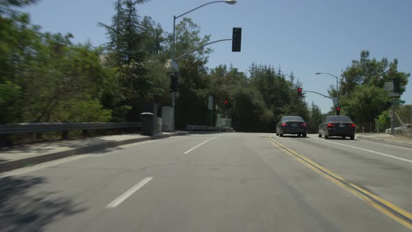 Rear view of a Driving Plate: Car travels eastbound on Colorado Boulevard  in Pasadena, California, crosses Colorado Street Bridge and continues to  the