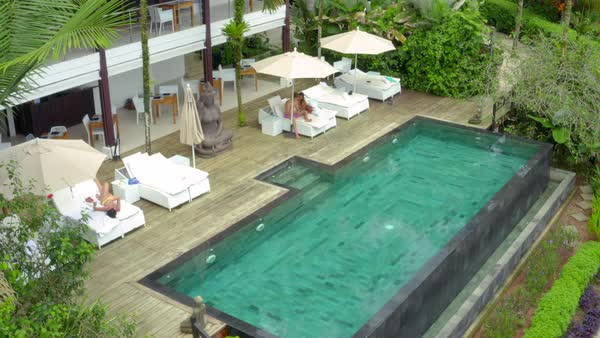 Aerial Young People Relaxing By Swimming Pool Among Lush Green