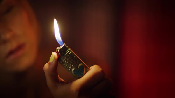 Close-up shot of a woman lighting a cigarette lighter and looking at flame,  California, United States of America stock footage
