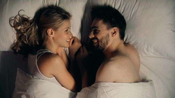 Close up of young couple lying in bed facing each other and talking Royalty-free stock video