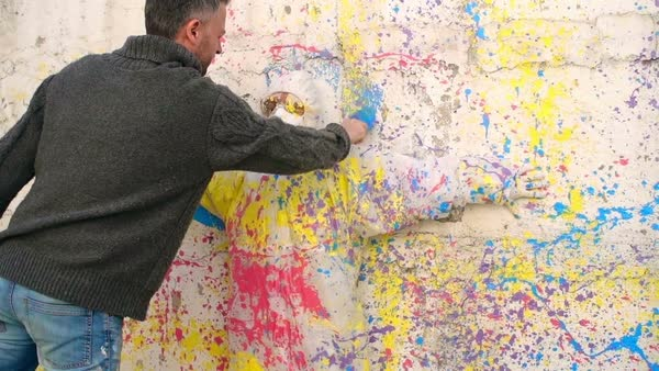 Artist Painting An Outline Of A Model On A Paint Splatter Wall Stock Footage