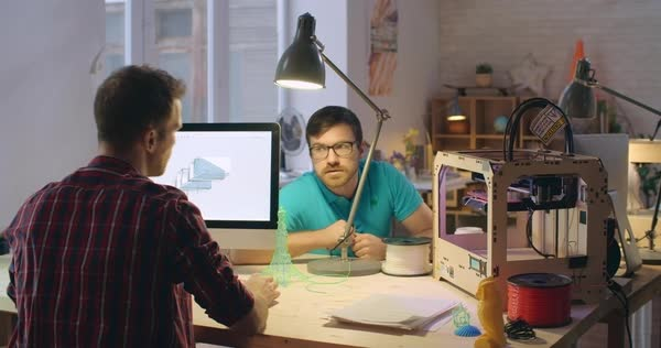 Two engineers collaborating in 3d printing laboratory: designing 3d models  on computer, printing them and discussing documentation stock footage