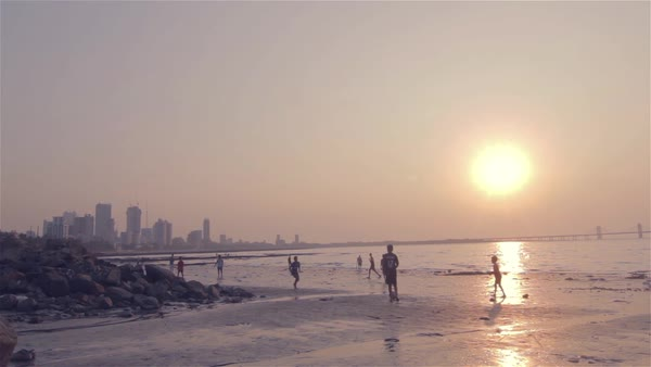 Children playing football near the sea in the evening. (Mumbai, India) Royalty-free stock video