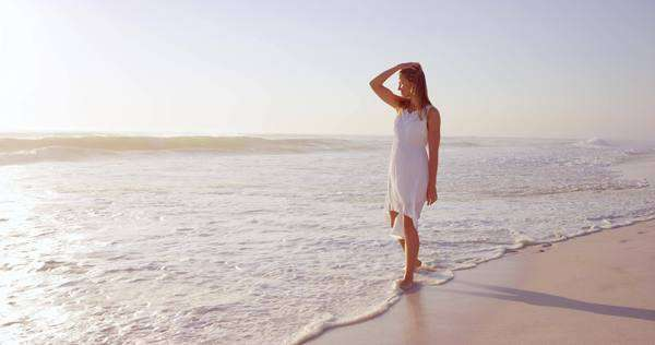 Beautiful woman wearing white dress walking on beach at sunset in slow motion Royalty-free stock video