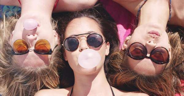 Top view of three teeanage girl friends lying on back blowing bubblegum candy bubbles on beach Royalty-free stock video