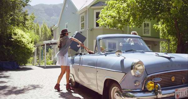 Two beautiful girl friends packing a vintage convertible car and leaving for road trip Royalty-free stock video