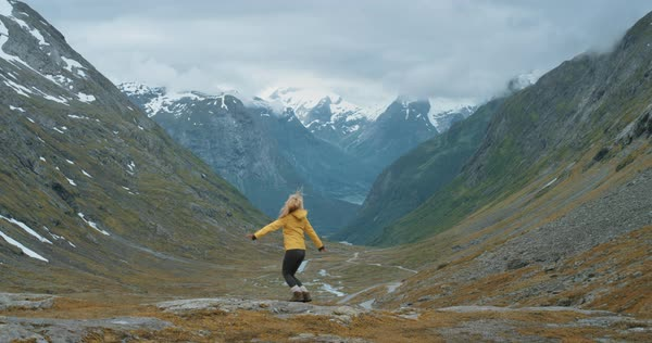 Woman dancing silly freestyle dance outdoors on mountain Crazy dancer having fun traveller enjoying nature celebrating vacation travel adventure Norway Royalty-free stock video