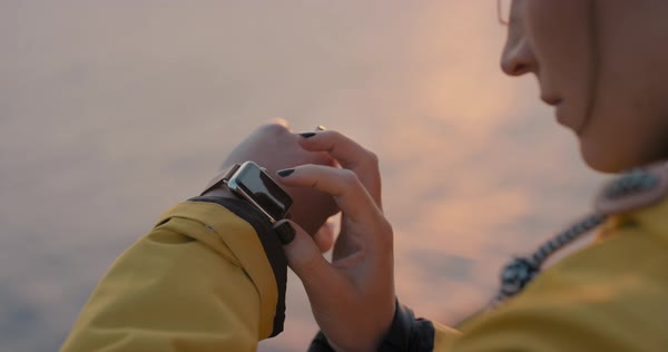 Close-up woman using smartwatch at sunset making connection sending message text ocean view with soft light lens flare landscape nature background enjoying vacation adventure Royalty-free stock video