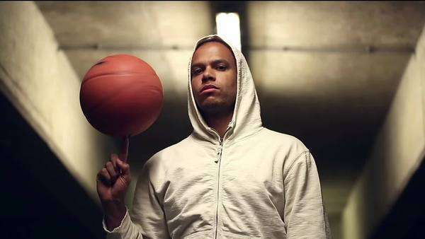 Hooded basketball player spinning a ball under a light Royalty-free stock video