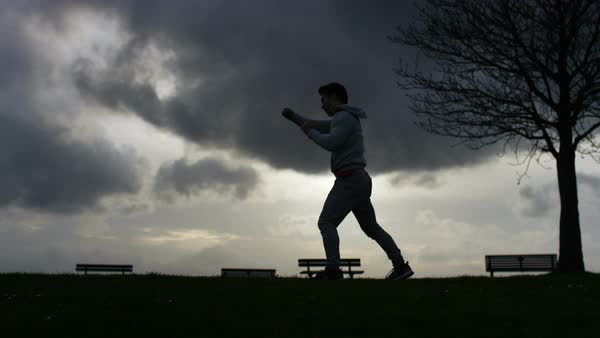 Male silhouette fight training against dark clouds, in slow motion Royalty-free stock video