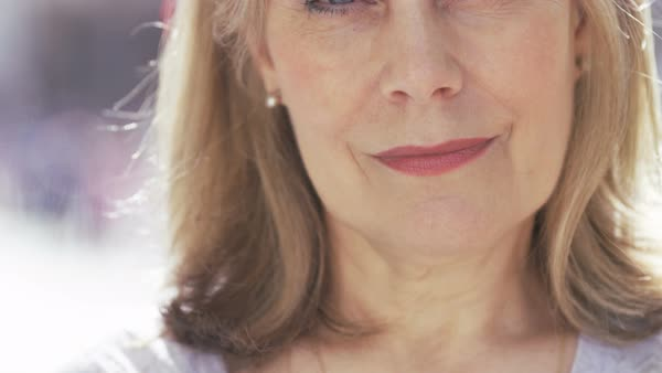 Portrait of attractive mature woman looking to camera and smiling, in slow motion Royalty-free stock video