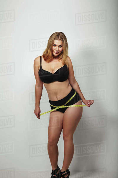 55ba47f5b69 Positive overweight woman measuring her hip with tape measure. Plus size  woman in bikini checking her size on grey background. - Stock Photo -  Dissolve