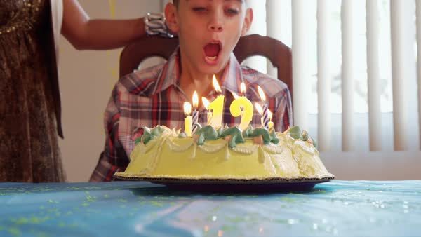 Boy Blowing Out Candles On Cake For His 12th Birthday Slow Motion