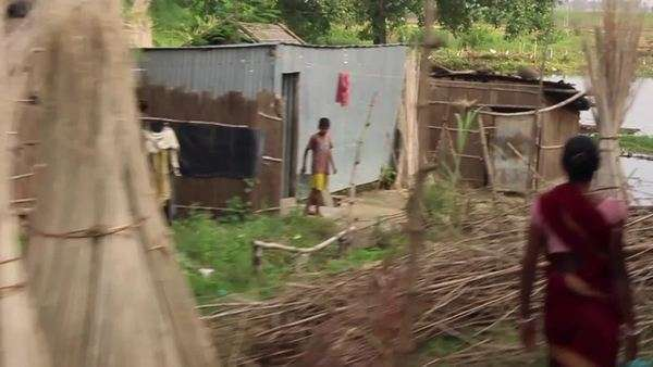 Passing by farmers and villages in India  Filmed in the countryside of  Bengal, India, from a moving train, in slow motion  stock footage