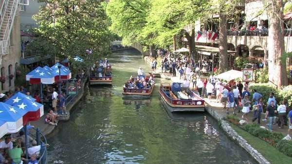 San Antonio Texas Riverwalk Tourists At Restaurants And S Walking Along Sidewalk Floating Barge Boats Walkways With Stone Foot Bridges