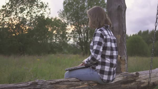 Woman using laptop computer while sitting on log in park in the evening  stock footage