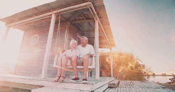 Happily retired senior couple holding hands together while sitting in their porch swing with sun flare, panning in slow motion Royalty-free stock video