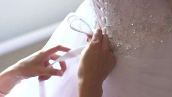 Handheld shot of a woman tying a bride's dress Royalty-free stock video
