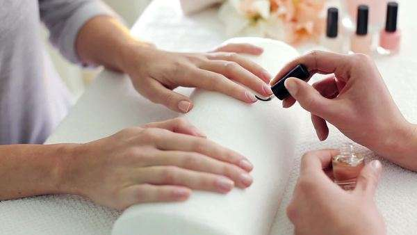 Beautician applying transparent nail polish onto a customer's nails. Royalty-free stock video