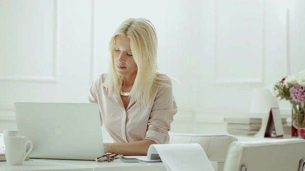 Blonde Caucasian businesswoman sitting at her desk and working. Royalty-free stock video