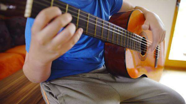 Boy in blue shirt play guitar while sit on table  Young person practice  guitar instrument at home while sitting on table in living room  Acoustic  old