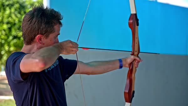 Man First Time Shooting With Bow And Arrow Male Person Stretching String Releasing To Hit A Target