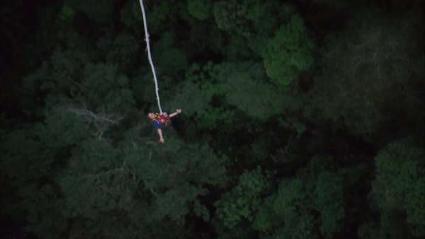 High angle slow motion shot of a person bungee jumping with their arms outstretched to the side, and giving a thumbs up sign as she come up Rights-managed stock video