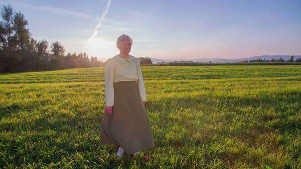 grass field sunset. Old Senior Woman Standing On A Field At Sunset. In Front Of The Camera Grass Sunset And Wind Blowing To Her Skirt