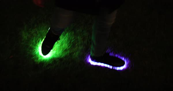 Hand-held shot of a person walking in glowing shoes Royalty-free stock video