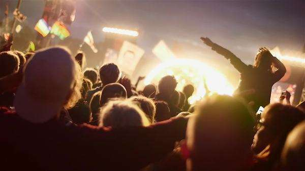Crowd enjoying themselves at outdoor music festival, girl wavering in slow motion Royalty-free stock video