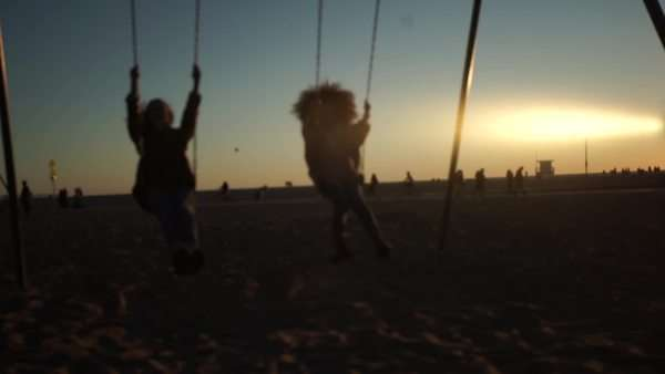 Handheld shot showing a man and a woman jumping from moving swings at sunset Royalty-free stock video