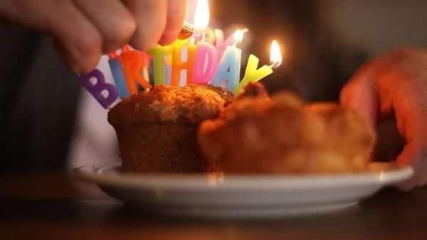 Tilting shot of lighting candles on birthday muffins Royalty-free stock video