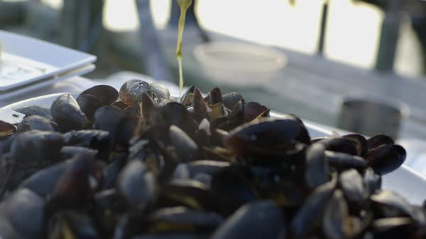 Close-up shot of a person pouring sauce on mussels Royalty-free stock video