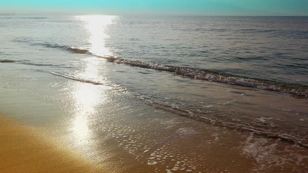 Seamless loop of ocean waves on a sandy beach as people walk by stock  footage