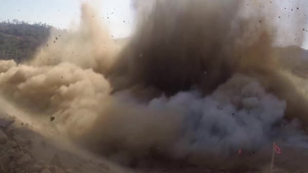 Ground level shot of a dynamite explosion clearing a water channel at the  Oroville dam spillway reconstruction project  stock footage