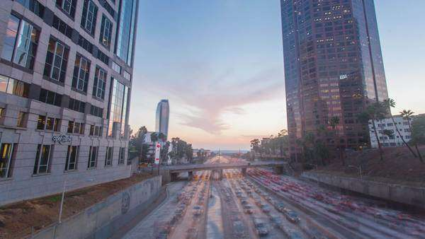 DOWNTOWN, LOS ANGELES, CALIFORNIA, USA - 07 OCTOBER 2014, Hyperlapse video view on beautiful sunset over business buildings and rush hour freeway traffic jam. Transition from day to night. Royalty-free stock video