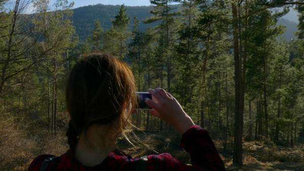 A young girl takes a picture in the woods Royalty-free stock video