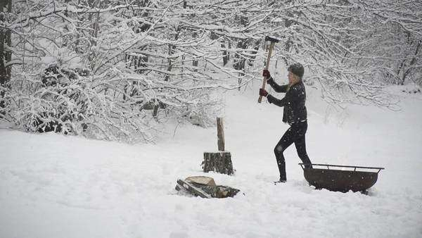 Slow motion woman chopping wood in snow Royalty-free stock video
