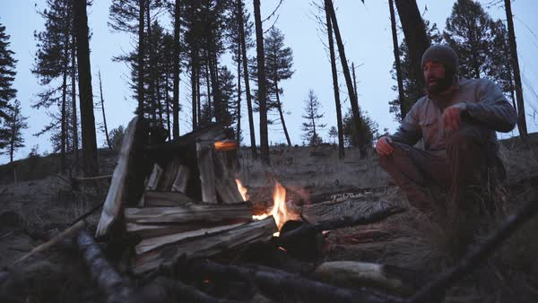 Hand-held shot of a man warming himself at a campfire Royalty-free stock video
