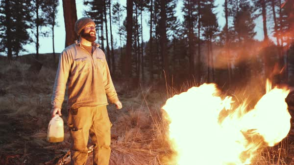 Hand-held shot of a man pouring fuel on a campfire Royalty-free stock video