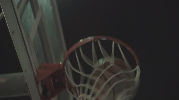 Hand-held shot of a person shooting a basketball at night Royalty-free stock video
