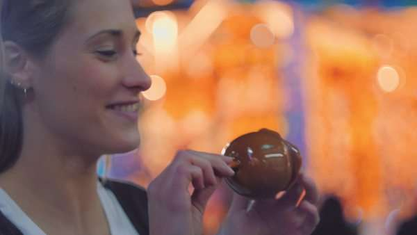 Handheld shot of a woman eating chocolate dipped apple on a fair Royalty-free stock video