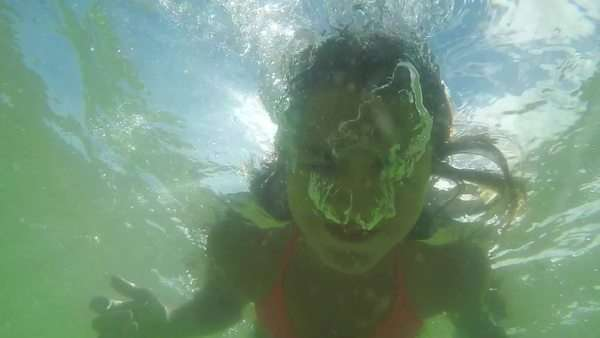 Teenage girl puts her head underwater (in ocean) and blows bubbles at camera Royalty-free stock video