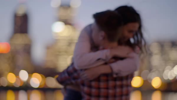 Playful couple dance on a dock across from city, man twirls his girlfriend and surprises her with a kiss on her hand, she laughs Royalty-free stock video