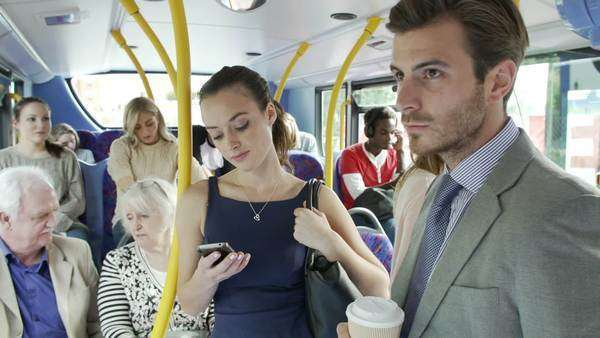 Interior of busy commuter bus with businesspeople texting on mobile phone and drinking coffee. Royalty-free stock video