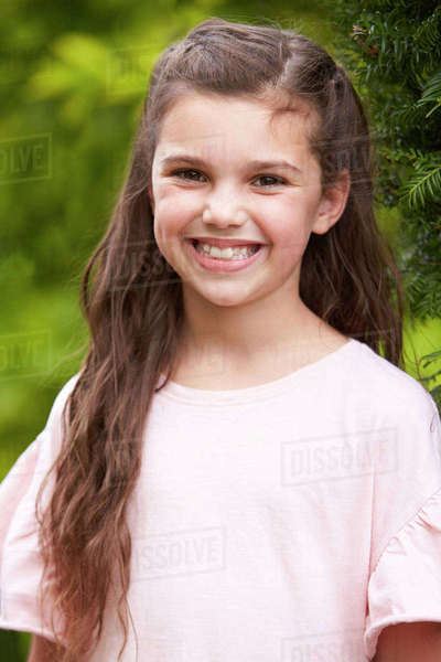 Portrait Of Smiling Young Girl Standing Outdoors In Garden