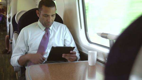Camera pans from businessman using digital tablet to fellow passengers in next seat using mobile phone or asleep. Royalty-free stock video
