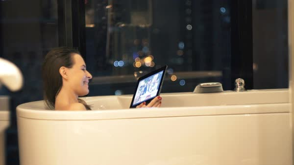 Happy Woman Watching Movie On Tablet During Bath At Night